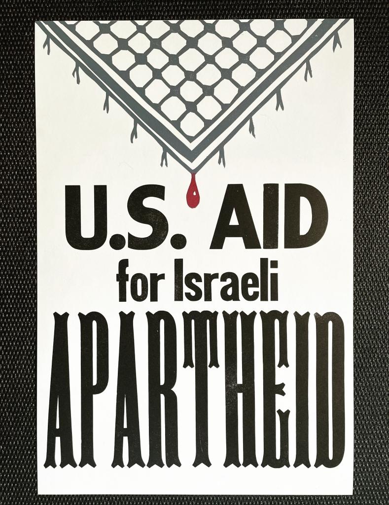 "Khaffiya with blood drop; wood type says ""US Aid for Israeli APARTHEID"" below"